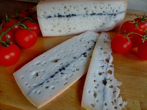 Tvrdý sýr s mazem linkou uhlí a oky -na řezu